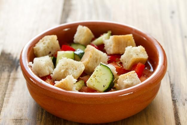 Portugiesisches gaspacho in der schüssel in der braunen holzoberfläche