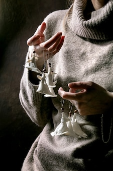 Porzellan weihnachtsengel. frau im wollpullover halten auf den fingersätzen des weißen handwerks handgemachte weihnachtsengeldekoration.