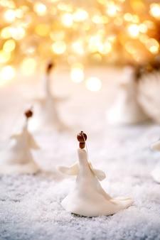 Porzellan weihnachtsengel. satz handgefertigte weihnachtsdekoration auf schnee mit bokeh-feiertagslichtern