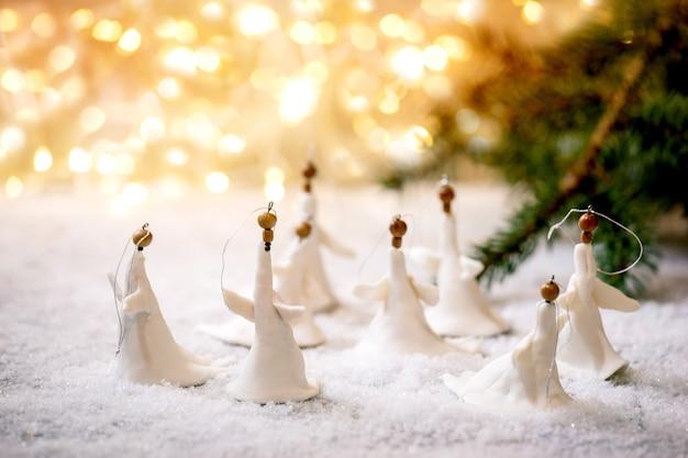 Porzellan weihnachtsengel. satz handgefertigte weihnachtsdekoration des handwerks auf schnee mit bokeh-feiertagslichtern und tannenzweigen.