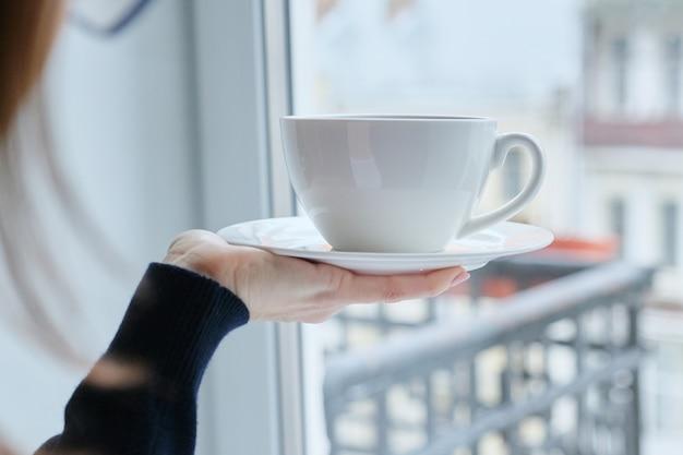 Porzellan weiße tasse auf einer untertasse in frauenhand, eingestellt