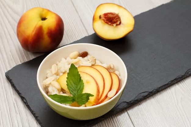 Porzellanschüssel mit sorghumbrei, frischem pfirsich, cashewnüssen, mandel- und minzblättern auf steinbrett und grauem holztisch. veganer glutenfreier sorghumsalat mit frischen früchten. ansicht von oben.