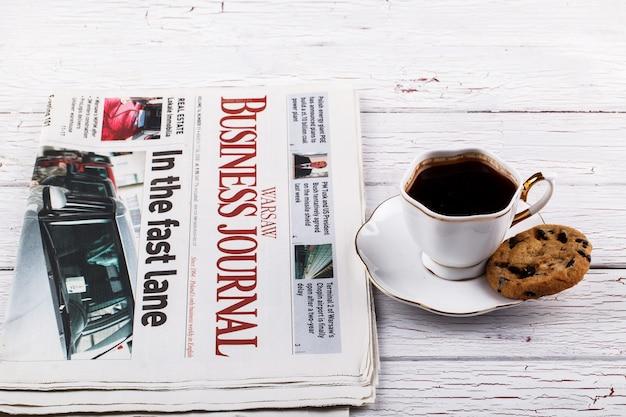 Porzellantasse mit kaffee steht vor zeitungen und einem buch