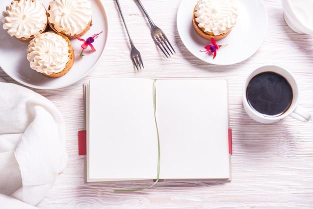 Porzellanteller mit kuchen und geöffnetem buch, notizbuch, buch