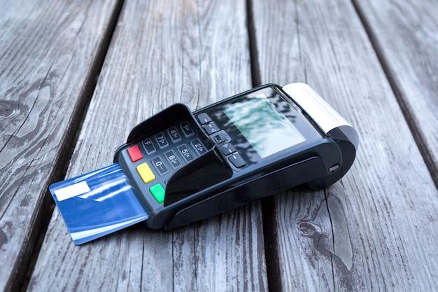 Pos-terminal, hand, die kreditkarte, zahlung mit nfc-technologie auf holztisch klaut