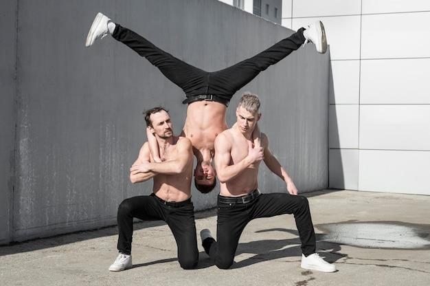 Pose von drei hemdlosen hip-hop-tänzern draußen