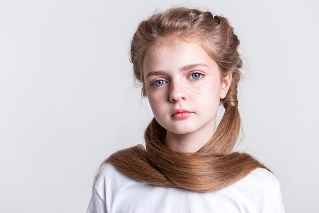 Posieren für die kamera. ansprechendes, gut aussehendes junges mädchen, das sich mit langen haaren bedeckt, während es eine komplexe frisur hat