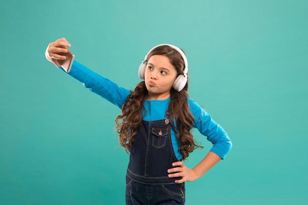 Posieren für ein foto. selfie-kind in kopfhörern. videoanruf für kleine kinder auf dem smartphone. kleines mädchen hält handy. bloggen im modernen leben. schulmädchen verwenden neue technologie. in der virtuellen welt leben.