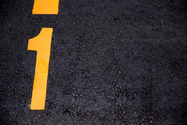 Position 1 farbe auf asphaltstraße hintergrund mit exemplar