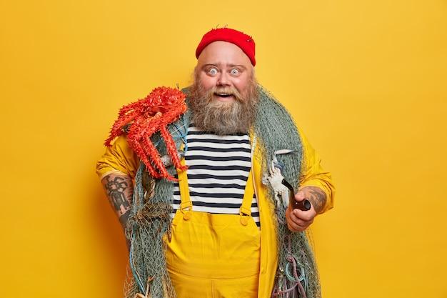 Positiv beeindruckter bärtiger seemann in gestreiften weste posiert mit rotem tintenfisch auf der schulter, hält pfeife, trägt fischernetz