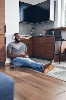 Positiv begeisterte junge männliche person, die auf dem boden sitzt und sich an die wand lehnt, während sie musik hört