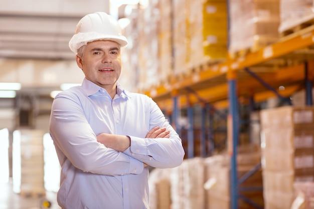 Positiv begeisterter geschäftsmann, der einen helm trägt, während er den arbeitsprozess im lager kontrolliert