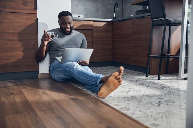 Positiv begeisterter mann, der eine tasse mit kaffee in der rechten hand hält, während er auf den bildschirm seines laptops schaut