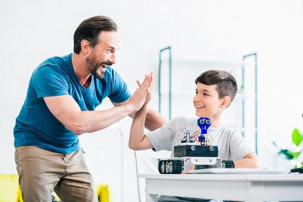 Positiv begeisterter vater, der seinem sohn high five gibt, während er sein ingenieurprojekt für einen modernen roboter beendet
