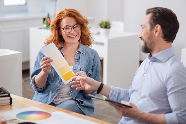 Positiv entzückte rothaarige frau, die am tisch sitzt und sich mit ihrem kollegen bei der auswahl der farbe berät