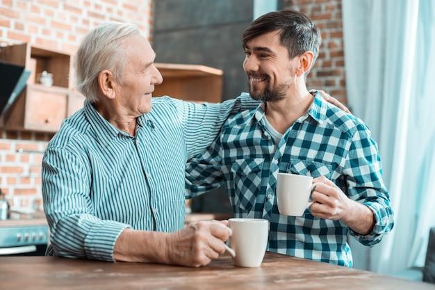 Positiv entzückter glücklicher glücklicher vater und sohn, die lächeln und einander ansehen, während sie zeit zusammen verbringen