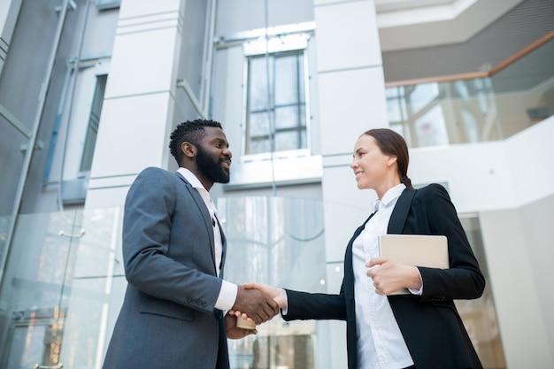 Positiv erfolgreicher afroamerikanischer geschäftsmann im anzug händeschütteln mit hübscher geschäftskollegin, während er sie in gesellschaft begrüßt