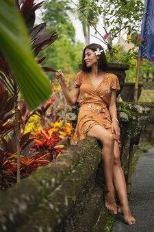 Positiv erfreute weibliche person, die auf der stütze sitzt und während der fotosession exotische blätter berührt
