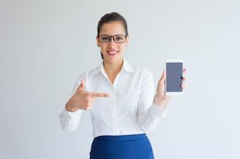 Positiv erfüllte den jungen weiblichen Manager, der auf Gerätschirm zeigt.