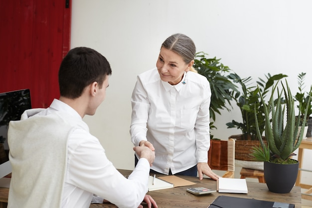 Positiv freundlich aussehende reife weibliche hr-spezialistin, die an ihrem schreibtisch steht und hand des nicht erkennbaren männlichen bewerbers nach erfolgreichem vorstellungsgespräch schüttelt. rekrutierung und personal