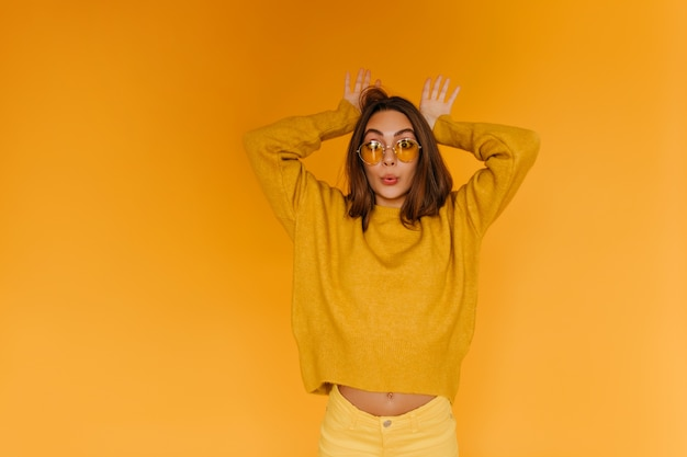 Positiv gebräuntes mädchen in der sonnenbrille, die lustige gesichter auf orange wand macht. innenporträt der fröhlichen braunhaarigen frau trägt orangefarbenen pullover.