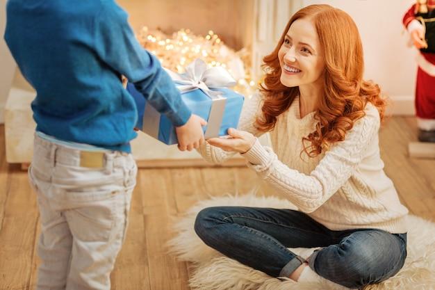 Positiv gesinnte mutter, die fröhlich lächelt, während sie ihren kleinen sohn mit augen voller liebe ansieht und ein wunderschön verpacktes geschenk erhält.