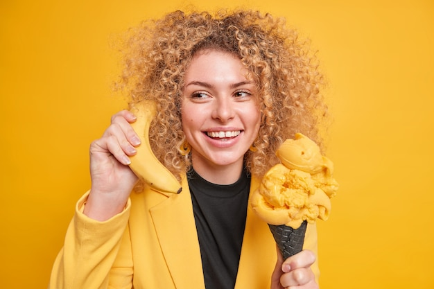 Positiv gut aussehende frau hat naschkatzen hält leckeres gefrorenes dessert genießt es, eis zu essen, hält reife banane in der nähe von essen, als ob das telefon lächelt, trägt stilvolle outfit-posen gegen die gelbe wand