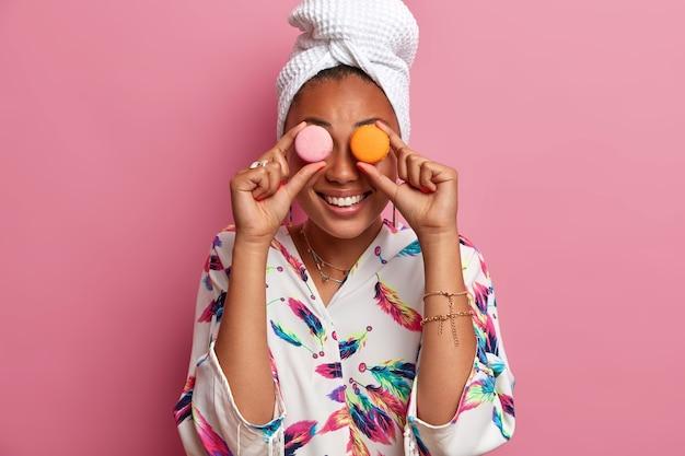 Positiv lächelnde dunkelhäutige frau bedeckt die augen mit köstlichen süßen makronen, bekommt kalorien, isst gerne süßes essen, trägt ein badetuch auf dem kopf, lässige hausrobe. frauen- und diätkonzept