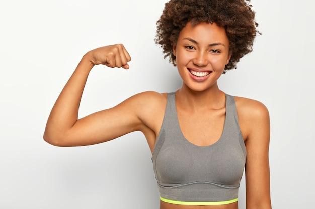 Positiv lächelnde junge frau gemischter rasse hebt muskulösen arm, zeigt bizeps, hat ein kraftvolles aussehen, lächelt glücklich, trägt einen sport-bh, isoliert über weißem hintergrund, sagt, wie stark ich bin.
