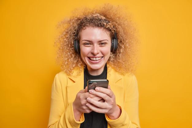 Positiv lächelnde junge lockige frau hält handy prüft e-mail-box, die gut gelaunt ist, hört musik über kopfhörer, die formell gekleidet ist, genießt die freizeit isoliert über leuchtend gelber wand