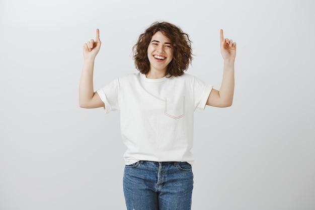Positiv lächelndes mädchen zeigt copyspace, lächelt und zeigt mit den fingern nach oben