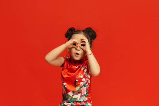 Positiv posieren, nach geschenken suchen. . asiatisches niedliches kleines mädchen lokalisiert auf roter wand in traditioneller kleidung. feier, menschliche gefühle, feiertagskonzept. copyspace.