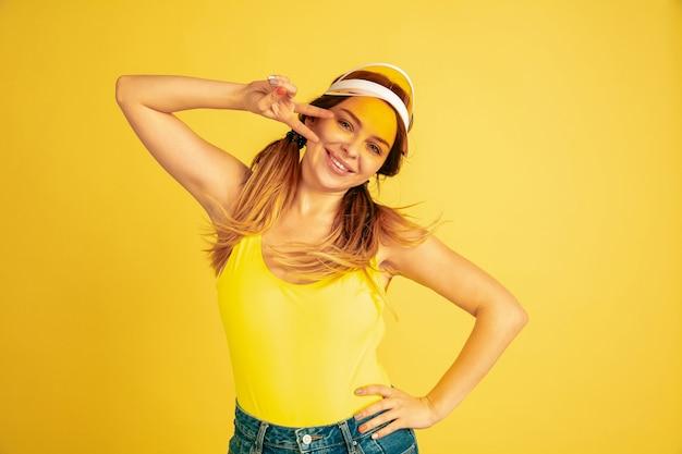 Positiv posierend, lächelnd. porträt der kaukasischen frau auf gelbem studiohintergrund.