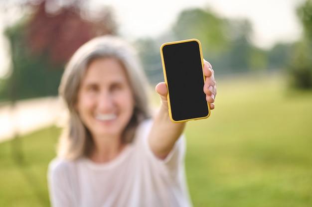 Positiv. smartphone-bildschirm in ausgestreckter hand einer lächelnden frau in guter laune an einem schönen tag im freien