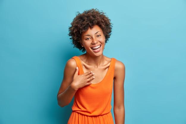Positiv unterhaltene dunkelhäutige junge frau lacht laut auf