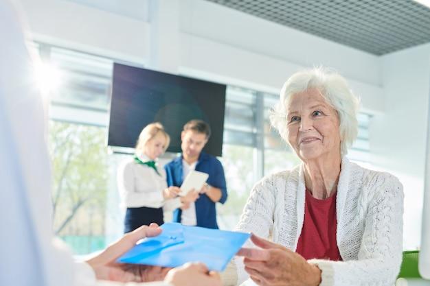 Positive ältere dame, die umschlag mit dokumenten in bank erhält