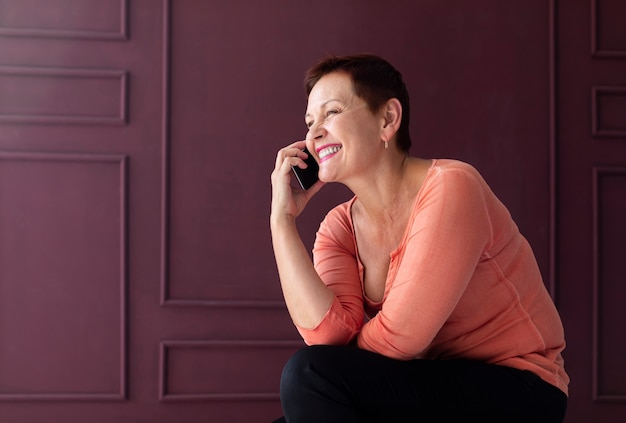 Positive ältere frau, die am telefon spricht