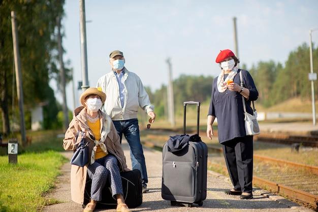 Positive ältere senioren menschen mit gesichtsmasken warten zug vor der reise