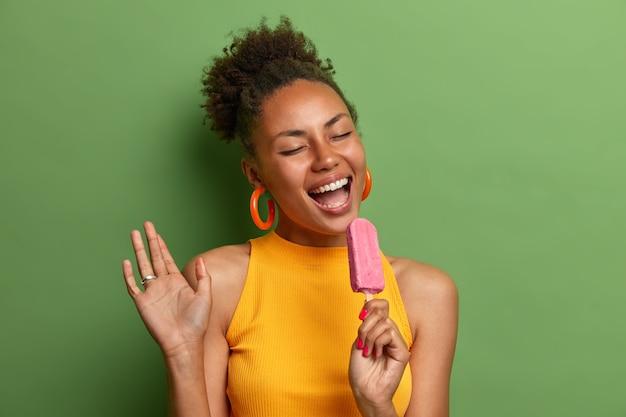 Positive afroamerikanerfrau kühlt mit kaltem erdbeereis isoliert