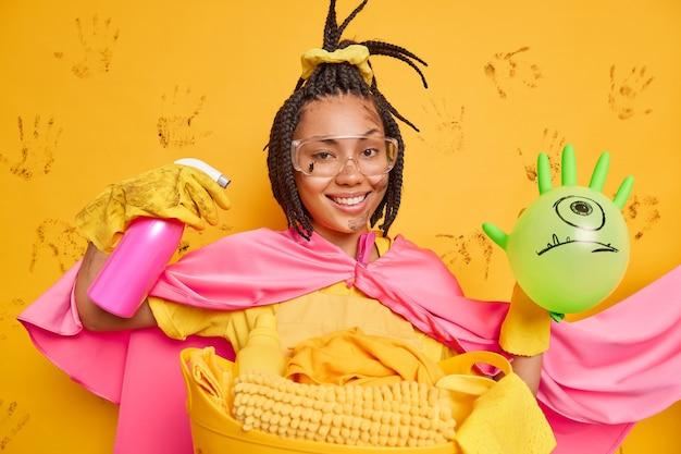 Positive afroamerikanerin gibt vor, superheldin zu sein, rettet die welt vor schmutz verwendet reinigungsmittel hält lustigen ballon mit gezeichnetem gesicht steht schmutzig gegen gelbe wand