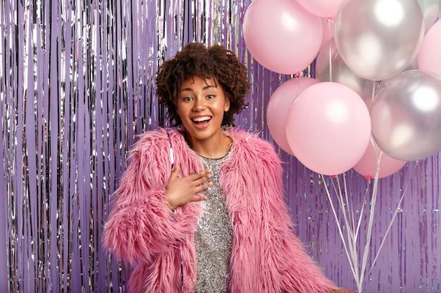 Positive afroamerikanerin kommt, um freund zum jubiläum zu gratulieren, hält luftballons, hält hand auf brust