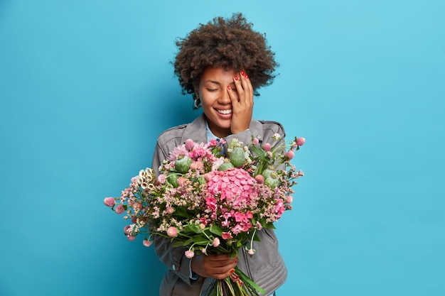 Positive afroamerikanische frau hält schönen blumenstrauß erhalten auf geburtstag bedeckt gesicht mit hand gekleidet in grauer jacke über blaue wand isoliert