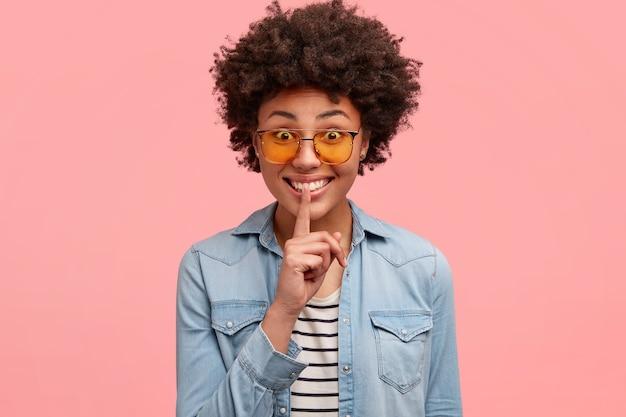 Positive afroamerikanische frau legt zeigefinger auf die lippen, macht stilles zeichen, wie geheimnis verrät, hat glücklichen ausdruck, gekleidet in modische kleidung, zeigt lockiges haar und weiße zähne, isoliert auf rosa