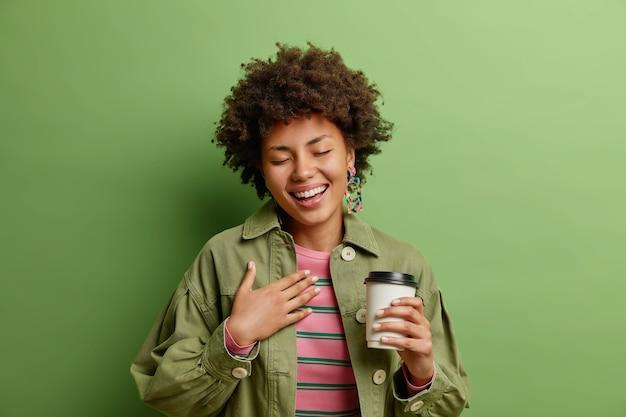 Positive afroamerikanische frau mit lockigem haar schließt die augen vor glück hält hand in der nähe des herzens getränke zum mitnehmen kaffee genießt freizeit gekleidet in modische kleidung isoliert auf grüner wand