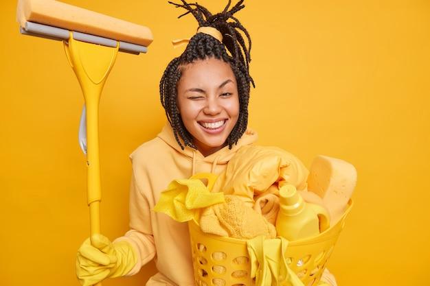 Positive afroamerikanische hausfrau zwinkert mit den augen und lächelt im großen und ganzen hat glückliche stimmung
