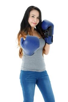 Positive aktive junge asiatische frau in lässigem outfit und blauen boxhandschuhen, die in die kamera stanzen, während sie einen gesunden lebensstil vor weißem hintergrund praktiziert
