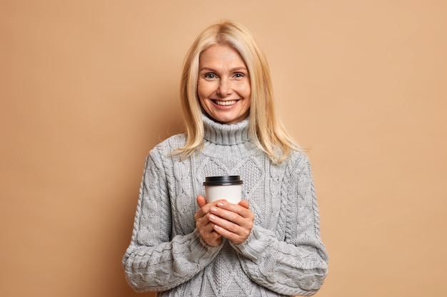 Positive angenehm aussehende frau mit blonden haaren hält einweg tasse kaffee genießt es, heißes getränk bei kaltem winterwetter zu trinken, gekleidet in gestrickten grauen pullover.