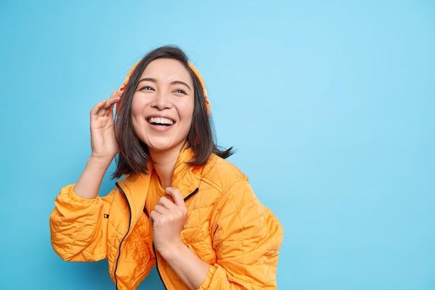 Positive asiatische frau genießt lieblingsmusik in kopfhörern lächelt breit ausdruck des glücks trägt orangefarbene jacke isoliert über blauem hintergrund mit kopienraum für ihre werbung. lebensstil