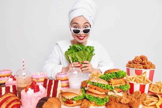 Positive asiatische frau hält salatblätter umgeben von fast food
