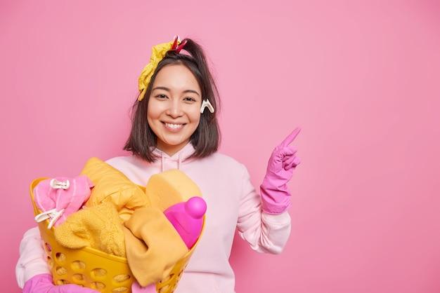 Positive asiatische frau mit fröhlichen ausdruckswäscheklammern auf dem haar hält waschbecken mit wäsche, die damit beschäftigt ist, hausarbeit zu machen